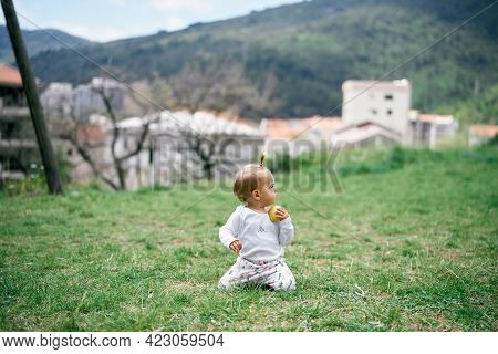 Little Girl Kneels On A Green Meadow With An Apple In Her Hand Against The Background Of Houses