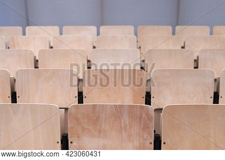 Empty Collapsible Wooden Chairs In Auditorium Background. Higher Education At University Or College.