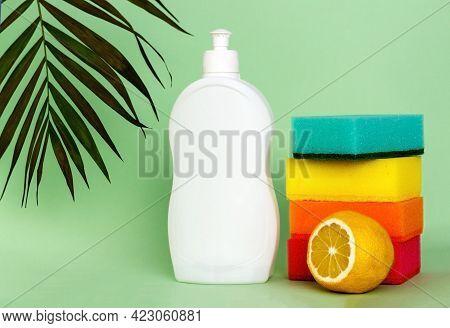 Plastic Bottle Of Dishwashing Liquid, Lemon And Sponges On Color Background. Washing And Cleaning Co