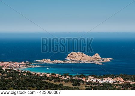 Turquoise Mediterranean Sea Surrounds The Red Rock And Harbour At La Pietra In Ile Rousse In The Bal