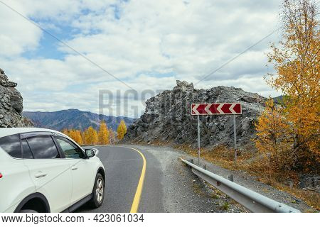 Car On Mountain Highway Between Rocks And Trees With Yellow Foliage In Autumn. Vivid Landscape With