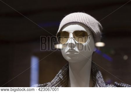 Mannequin In A Knitted Hat And Dark Glasses, Trendy Modern Look, Glare And Blur From Glass And Lamps