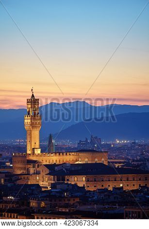 Florence, Tuscany, Italy. Tower of Palazzo Vecchio at evening after sunset. Evening illumination on the ancient walls. High mountains on the horizon.