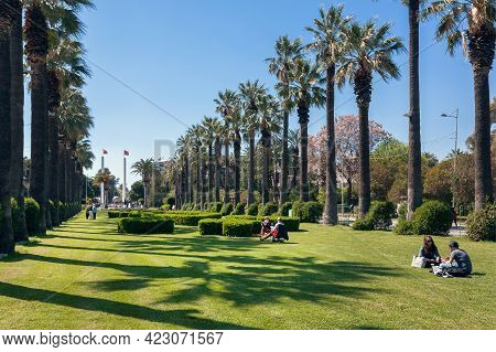 Izmir, Turkey: People Are Resting On The Grass Of The Park, Under The Palm Trees On A Sunny Day On 2