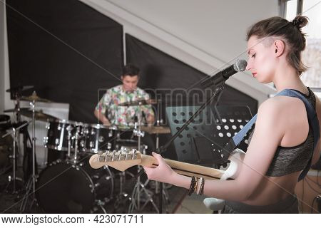 Rock Band Rehearsal In A Studio. Audio Sound Check. Teen Boy Playing Drums And Female Guitarist With