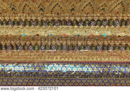 Details Of The Decoration Of The Wall Of A Buddhist Temple. On A Gilded Background, There Are Patter