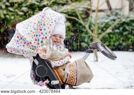Cute Little Beautiful Baby Girl Sitting In The Pram Or Stroller On Cold Snowy Winter Day. Happy Smil