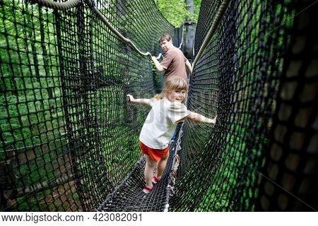 Little Preschool Girl And Father Walking On High Tree-canopy Trail With Wooden Walkway And Ropeways.