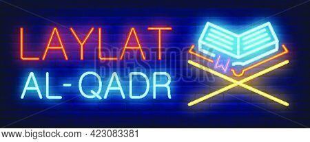 Laylat Al-qadr Neon Sign. Glowing Bar Lettering And Koran On Stand On Brick Background. Night Bright