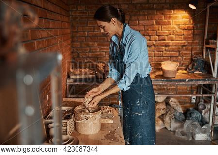 Young Caucasian Craftswoman Preparing Earthenware Material For Modeling In Pottery Workshop