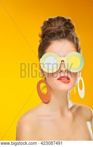 Pin-up style and beauty. Portrait of an exciting pretty woman posing in paper sunglasses and earrings in pin-up style on a yellow background. Makeup and cosmetics. Studio shot.