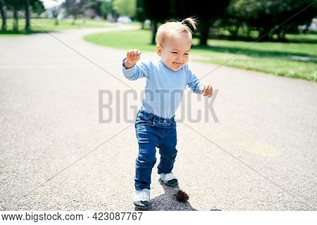 Laughing Little Girl With Ponytail Walking Along The Road In The Park