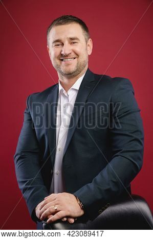 Handsome Caucasian Joyful Businessman Standing In The Studio On A Red Background Smiling Looking At
