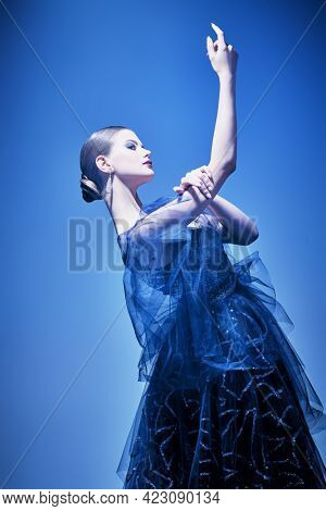 Beautiful graceful girl poses in a luxury evening dress in mixed colored light. Evening fashion. Studio portrait.
