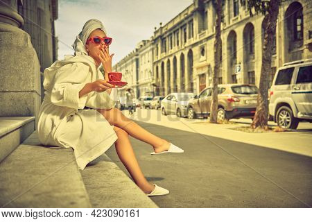 Glamorous lifestyle. Extravagant girl in a white bathrobe with a white towel on her head and elegant sunglasses alluring on a city street with a cup of tea and cigarette. Fashion shot.