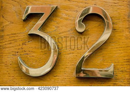 Brass Number Thirty Two On A Varnished Wooden Plaque On The Outside Wall Of A Building In Central Lo
