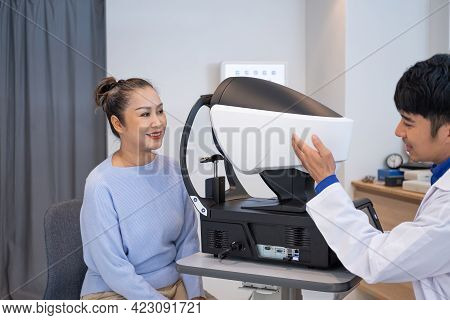 Doctor Using Penlight And Optometry Frame Equipment And Do Subjective Refraction To  Examine Eye Vis