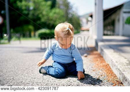 Little Girl Sits Near A Pavilion In The Park And Picks The Ground With Her Finger