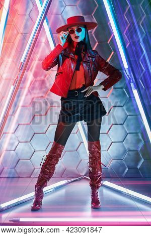 Fashion shot. Stunning fashion model girl in stylish leather clothes, red sunglasses and red hat poses among the neon lamps. Techno style. Full length portrait.