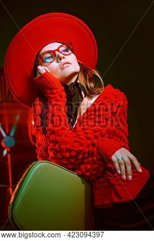 Portrait of a beautiful high fashion model girl posing in elegant red hat, cardigan and stylish glasses. New clothes collection. Optics style.