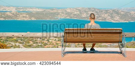 young caucasian man sitting in a bench in Palau, at the Northern coast of Sardinia, Italy, observes the Mediterranean sea and La Maddalena Archipelago, in a panoramic format to use as web banner