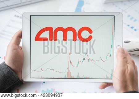 Russia Moscow 30.05.21 Tablet In Hands With Logo Of Amc Online Cinemas Network. Entertainment Holdin