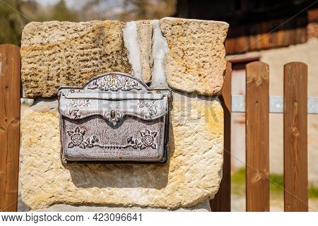 Vintage Wrought Iron Mailbox For Correspondence And Letters Weighs On A Stone Fence, Brown White Met