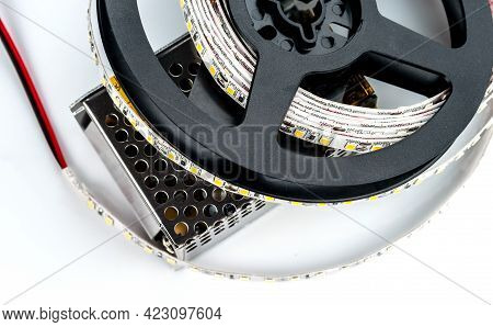 Reel With Led Strip With Power Supply For Voltage Of 12 Volts On A White  Background.