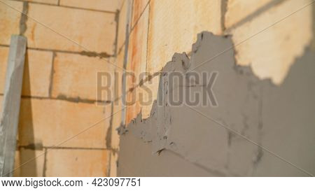 Applying The Putty Solution To The Wall. Close-up Of The Spatula For Applying The Solution To The Of