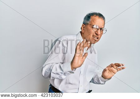 Middle age indian man wearing casual clothes and glasses disgusted expression, displeased and fearful doing disgust face because aversion reaction. with hands raised