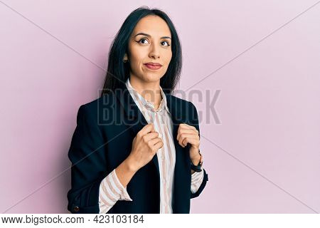 Young hispanic girl wearing business clothes smiling looking to the side and staring away thinking.
