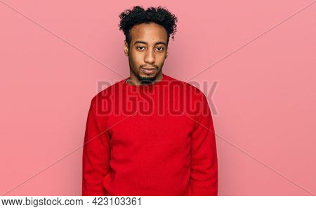 Young african american man with beard wearing casual winter sweater looking sleepy and tired, exhausted for fatigue and hangover, lazy eyes in the morning.
