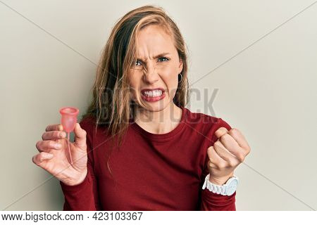Young blonde woman holding menstrual cup annoyed and frustrated shouting with anger, yelling crazy with anger and hand raised