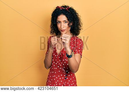Young latin girl wearing summer dress ready to fight with fist defense gesture, angry and upset face, afraid of problem