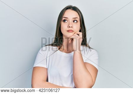 Young hispanic girl wearing casual white t shirt thinking concentrated about doubt with finger on chin and looking up wondering