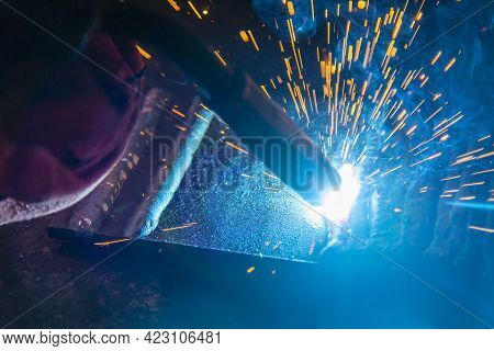 Close-up Scene Of The Electric Welding Process. The Welding Operation At Construction Site.