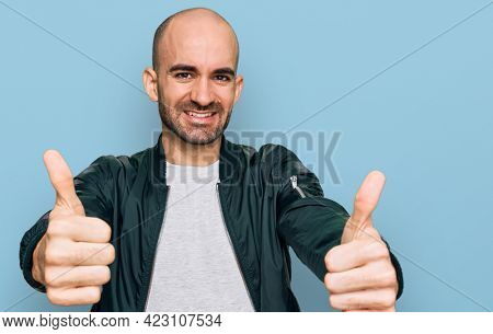 Young hispanic man wearing casual clothes approving doing positive gesture with hand, thumbs up smiling and happy for success. winner gesture.