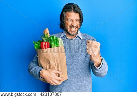 Middle age handsome man holding paper bag with groceries annoyed and frustrated shouting with anger, yelling crazy with anger and hand raised