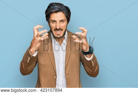 Young hispanic man wearing business clothes shouting frustrated with rage, hands trying to strangle, yelling mad