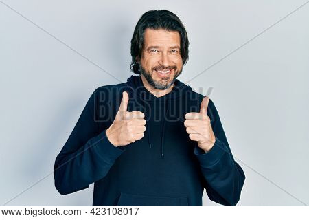 Middle age caucasian man wearing casual sweatshirt success sign doing positive gesture with hand, thumbs up smiling and happy. cheerful expression and winner gesture.