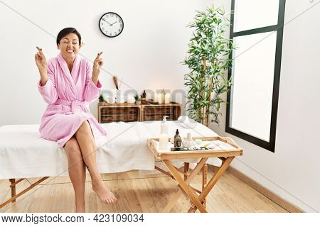 Beautiful caucasian woman wearing bathrobe at wellness spa gesturing finger crossed smiling with hope and eyes closed. luck and superstitious concept.