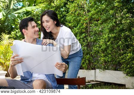 Asian Men And Women Couples Holding A Sheet Of Paper Blueprints For The Construction Of A New House
