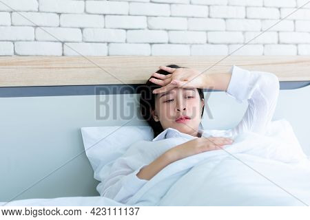 Asian Attractive Woman Lying In Bed, Using Hand Checking Forehead Temperature, Onset Of Flu Virus In