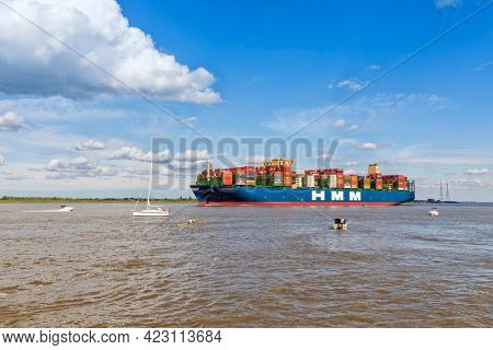 Stade, Germany - June 10, 2020:  Spectators on boats watching HMM ALGECIRAS,  the largest container ship worldwide, operated by Hyundai Merchant marine, on Elbe river near Hamburg.