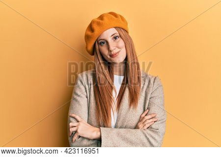 Young irish woman wearing french look with beret happy face smiling with crossed arms looking at the camera. positive person.
