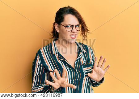 Young caucasian woman wearing casual clothes and glasses disgusted expression, displeased and fearful doing disgust face because aversion reaction. with hands raised
