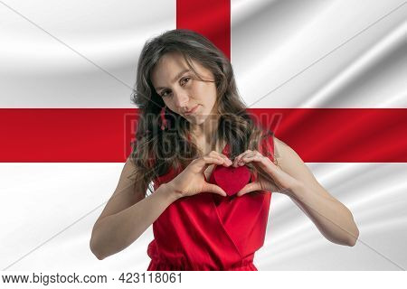 Love England. A Girl Holds A Heart On Her Chest In Her Hands Against The Background Of The Flag Of E