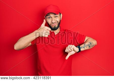 Hispanic man with beard wearing delivery uniform and cap doing thumbs up and down, disagreement and agreement expression. crazy conflict