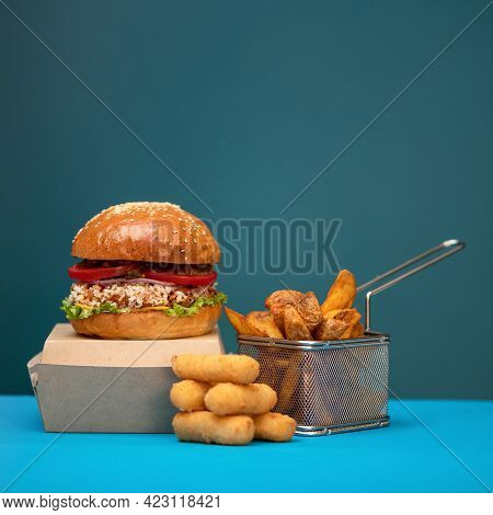 Ready-to-eat Takeaway Food. Cardboard Box With Fresh Hamburger, Fried Potatoes And Chicken Nuggets O