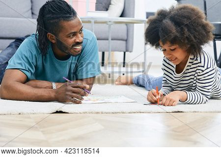 Dad And Daughter Drawing Pictures Together At House Floor. Fathers Day, Father-daughter Relationship
